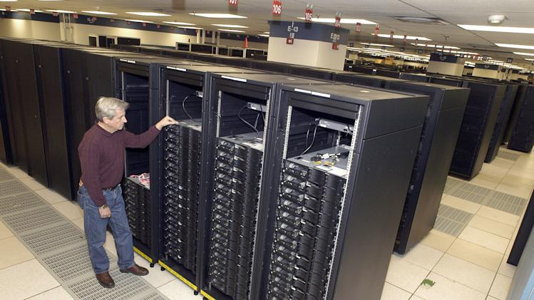 """This undated handout photo provided by IBM shows lead engineer Don Grice of IBM inspecting the world's fastest computer, nicknamed """"Roadrunner"""", in the company's Poughkeepsie, N.Y. plant.  It's the end of the line for the supercomputer that was once the fastest in the world and best known for breaking the once-elusive petaflop barrier.  Roadrunner, the $121 million supercomputer housed at Los Alamos National Laboratory will be decommissioned on Sunday, March 31, 2013. The reason: The world of supercomputing is evolving. Roadrunner's replacement is faster, more energy efficient and less expensive. (AP Photo/IBM via FPS, HO)"""