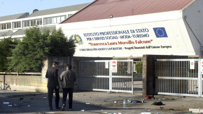"""An Italian Carabiniere, paramilitary police officer, left, walks on the site where an explosive device blasted outside """"Francesca Morvillo Falcone"""" high school in Brindisi, Italy, Saturday, May 19, 2012. ( AP Photo/Max Frigione)"""