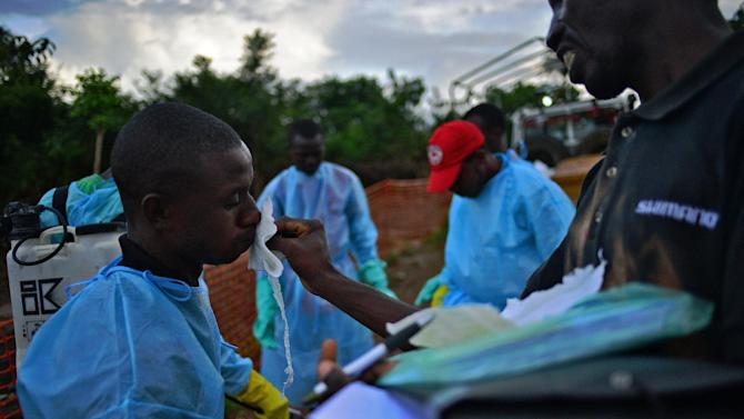 Sierra Leone health workers are disinfected after loading the bodies of Ebola victims onto a truck in Kailahun, on August 14, 2014