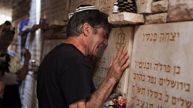 An Israeli man cries beside a memorial stone for a fallen soldier during the annual Memorial Day ceremony at the Mt. Herzl military cemetery in Jerusalem, Wednesday, April 25, 2012. (AP Photo/Bernat Armangue)