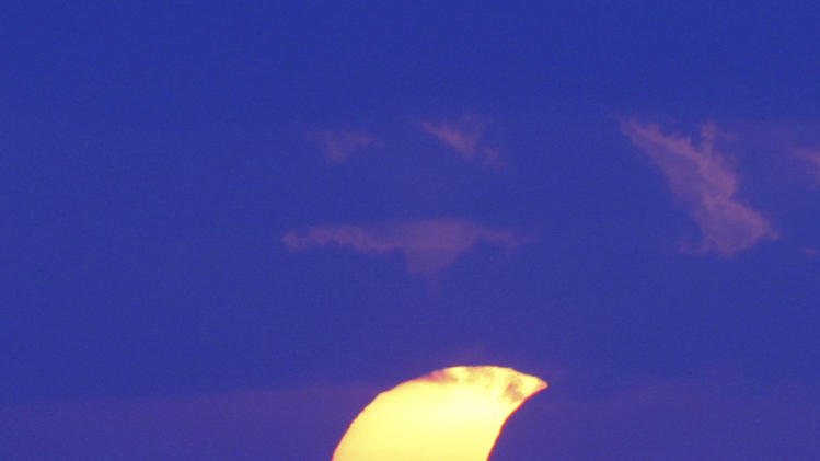 A partial solar eclipse is seen through cloud at Sanur beach, Bali, Indonesia, Friday, May 10, 2013. (AP Photo/Firdia Lisnawati)