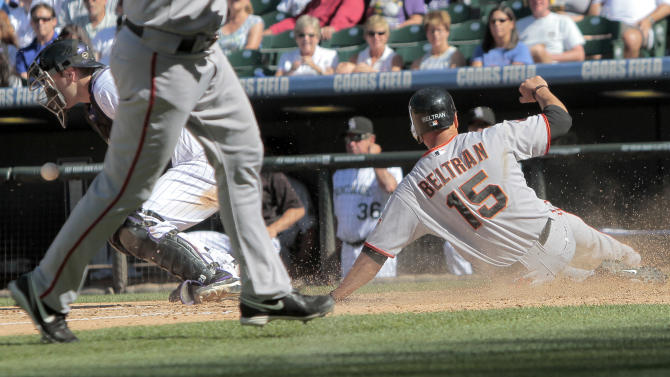San Francisco Giants right fielder Carlos Beltran (15) scores of a fielding error by Colorado Rockies' Chris Nelson with Chris Iannetta (20) guarding the plate during the sixth inning of a baseball game Sunday, Sept. 18, 2011 in Denver. The Giants won 12-5.  (AP Photo/Barry Gutierrez)