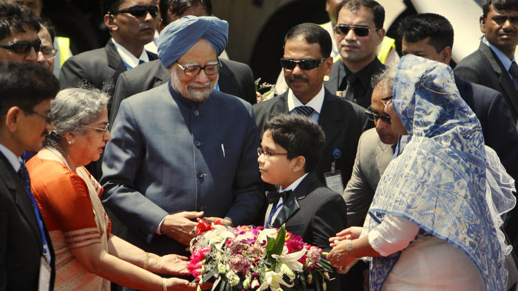 Bangladesh Prime Minister Sheikh Hasina, right, looks on as a Bangladeshi child presents flowers to Indian Prime Minister Manmohan Singh, center blue turban, and his wife Gursharan Kaur, second left, at Dhaka airport, Bangladesh, Tuesday, Sept. 6, 2011. Singh began a visit to Bangladesh on Tuesday aimed at warming often prickly ties between the two South Asian neighbors. (AP Photo/ Pavel Rahman)