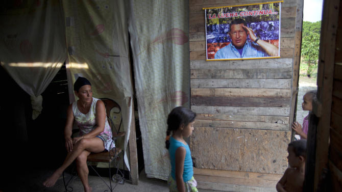 "In this April 8, 2013 photo, Yadaira Nunez, 43, sits in her wooden shack next to a poster of Venezuela's late President Hugo Chavez that reads in Spanish; ""The battle continues...,"" at a squatter settlement near Tacarigua, Venezuela. Outside Venezuela's capital, power outages, food shortages and unfinished projects abound; important factors heading into Sunday's election to replace Chavez, who died last month after a long battle with cancer. An estimated 2 million of Venezuela's country's nearly 30 million people lack permanent homes, and one of Chavez's anti-poverty ""missions"" builds them. But it's been slow going. The government says it has built 370,500 homes and apartments over the past two years, and more than 3 million people applied for them. (AP Photo/Ramon Espinosa)"