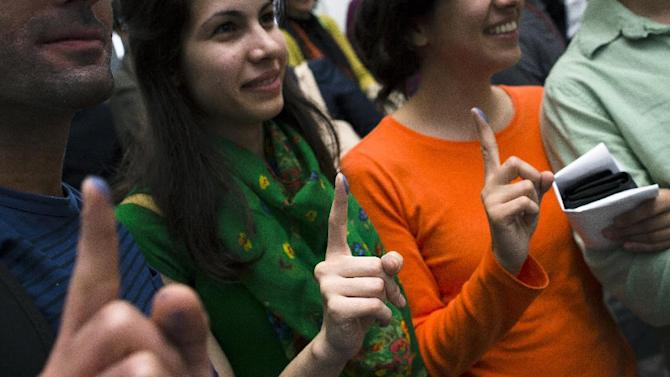 Iranians voters show their ink-stained fingertips at a polling station after casting their ballot for Iran's presidential election, Friday, June 14, 2013, in the Queens borough of New York. Iranian-Americans and expatriates will be able to vote Friday, but turnout is expected to be lower than in 2009 in part because there are fewer places to cast ballots. During the previous election, record numbers of Iranians voted in 41 locations throughout the U.S. This year, there are half as many voting locations. (AP Photo/John Minchillo)