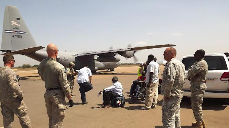 US army soldiers stand guard as a US army aircraft remains on the runway awaiting the arrival of American nationals who are being evacuated due to recent unrest and violence in South Sudan, on December 21, 2013, in Juba
