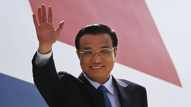 Chinese Premiere Li Keqiang waves as he arrives in New Delhi, India, Sunday, May 19, 2013. Just weeks after a tense border standoff, China's new premier arrived in India on Sunday for his first foreign trip as the neighboring giants look to speed up efforts to settle a decades-old boundary dispute and boost economic ties. (AP Photo/ Saurabh Das)