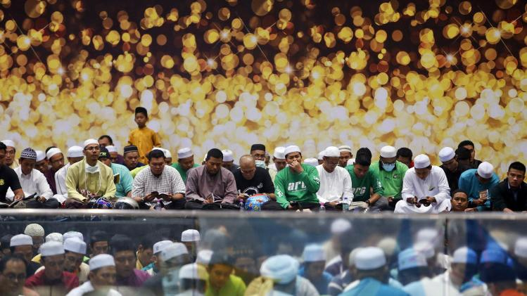 Muslims perform a special prayer for passengers of the missing Malaysia Airlines MH370 plane at the departure hall of the Kuala Lumpur International Airport