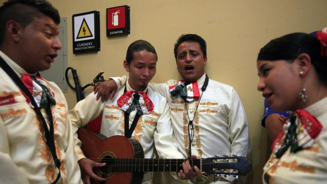 In this April 13, 2013 photo, members of El Rey Mariachi group rehearse in their dressing room inside the Mexico Theater in Quito, Ecuador. Mariachi music, one of the great folk genres of Mexico, has gained a strong following in the South America nation of Ecuador, and its practitioners here have come together to compete. Twelve groups initially signed up for the contest organized by the Mexican embassy in Ecuador, but in the end only seven showed up to participate after meeting the strict requirements. Each group had to have at least six members, and use at least six of the musical instruments traditionally played by mariachi bands.  (AP Photo/Dolores Ochoa)