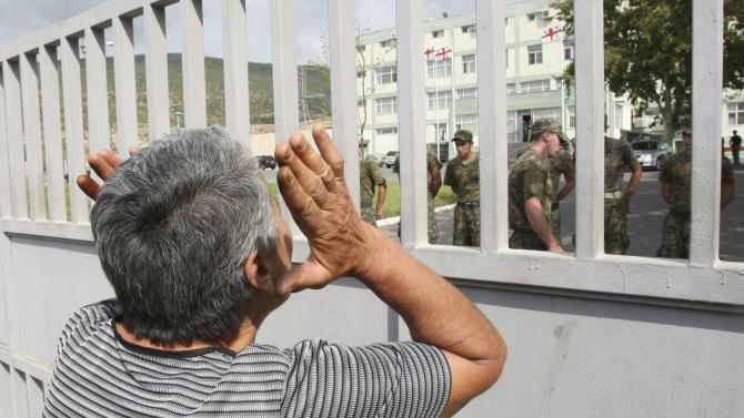 A woman shouts through a prison fence  during a protest rally against prison abuse in Tbilisi, Georgia, Thursday, Sept. 20, 2012. Street protests against the brutal abuse of prisoners escalated Thursday in the Georgian capital, fueling anger against the Western-allied government and possibly boosting support for the opposition before a tight parliamentary election. Two days after television stations aired videos of guards beating inmates and raping them with truncheons and brooms, thousands rallied outside the Interior Ministry and the Tbilisi prison where the abuse occurred. The protesters, some carrying brooms, then marched down the capital's main avenue to the presidential palace to demand the ouster of the interior minister. (AP Photo/Shakh Aivazov)