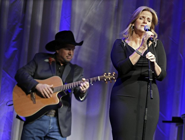 Trisha Yearwood is accompanied by her husband, Garth Brooks, as she sings &quot;Wind Beneath My Wings,&quot; a song written by Larry Henley, as Henley is inducted into the Nashville Songwriters Hall of Fame on Sunday, Oct. 7, 2012, in Nashville, Tenn. (AP Photo/Mark Humphrey)