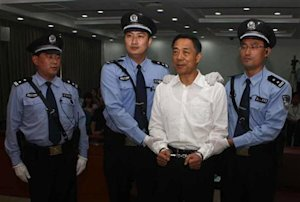 Ousted Chinese politician Bo Xilai is handcuffed after…