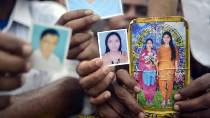 Family members hold portraits of their missing friends and family on Monday 29 April, 2013 in Savar, near Dhaka, Bangladesh. Rescue workers in Bangladesh gave up hopes of finding any more survivors in the remains of a building that collapsed five days ago, and began using heavy machinery on Monday to dislodge the rubble and look for bodies -- mostly of workers in garment factories there. At least 381 people were killed when the illegally constructed, 8-story Rana Plaza collapsed in a heap on Wednesday morning along with thousands of workers in the five garment factories in the building.(AP Photo/Ismail Ferdous)