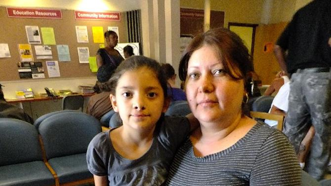 This photo taken July 16, 2012 shows Claudia Pedroza, 39, and her eight-year-old daughter Karla Osorio at the Jefferson Action Center in Lakewood, Colo. Pedroza moved to the Denver suburbs five years ago with her husband and four children in hopes of a more comfortable suburban life. But Pedroza's family struggles to make ends meet and she was waiting with her   on Monday, July 16, 2012, to apply for help with food, toiletries and seek a new frying pan. (AP Photo/Kristen Wyatt)