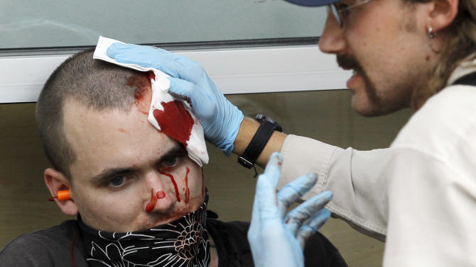 A protester is helped after sustaining an injury at a protest march and rally during this weekend's NATO summit in Chicago Sunday, May 20, 2012 in Chicago. (AP Photo/Charles Rex Arbogast)
