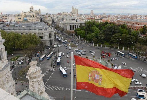 <p>A Spanish flag flies above Plaza de Cibeles in Madrid. Borrowing costs for Spain eased on Tuesday when it raised 4.86 bn euros in a sale of 12- and 18-month debt, a key test of confidence amid warnings the country may need bailing out.</p>