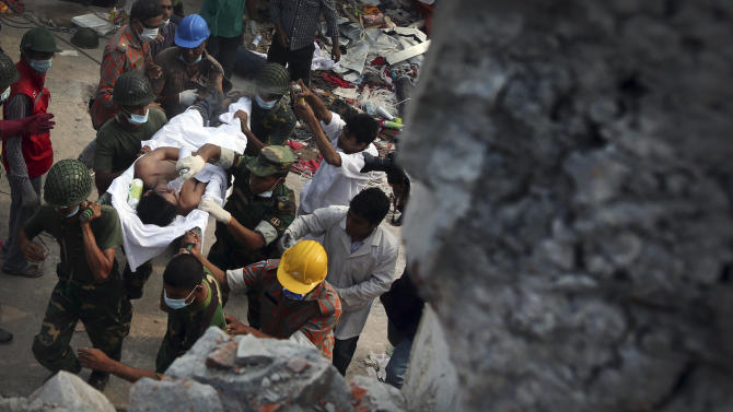 A survivor is evacuated from a garment factory building that collapsed Wednesday in Savar, near Dhaka, Bangladesh, Saturday, April 27, 2013. Police in Bangladesh took five people into custody in connection with the collapse of a shoddily-constructed building this week, as rescue workers pulled 19 survivors out of the rubble on Saturday and vowed to continue as long as necessary to find others despite fading hopes.(AP Photo/Wong Maye-E)