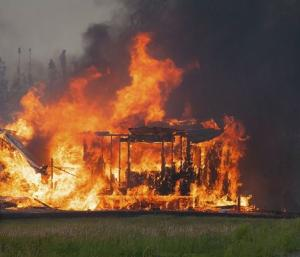 A structure is consumed by flames as an out of control…