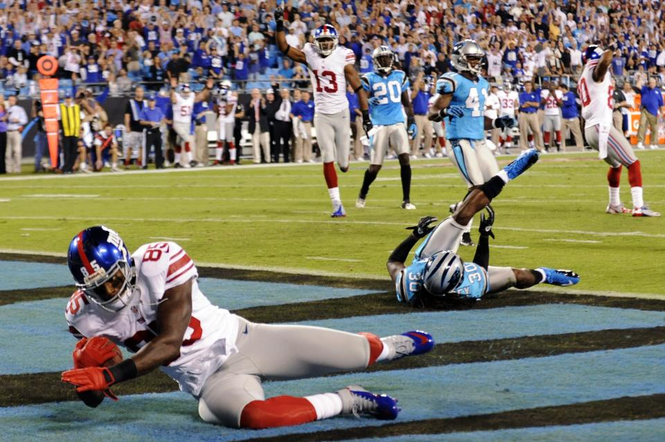 New York Giants wide receiver Martellus Bennett (85) catches a touchdown pass past Carolina Panthers safety Charles Godfrey (30) during the first quarter of an NFL football game in Charlotte, N.C., Thursday, Sept. 20, 2012. (AP Photo/Mike McCarn)