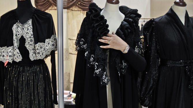 In this Saturday, April 13, 2013 photo, Emirati fashion designer Zaina al-Marzouqi covers a mannequin with an evening abaya during a bridal exhibition in Dubai, United Arab Emirates. The designer's abayas are selling between $700 to $1000. Just a few years ago, Gulf Arab women usually only felt comfortable showing off their fashion sense at ladies-only parties or family gatherings. In public, at least in their home countries, the standard all-black abaya _ a simple floor-length covering and accompanying head scarf _ was the only culturally accepted option. But now a new generation of abaya designers are giving the traditional garment a twist with choices of fabric, designs and even some expensive bling to allow Gulf women a host of style options.  (AP Photo/Kamran Jebreili)