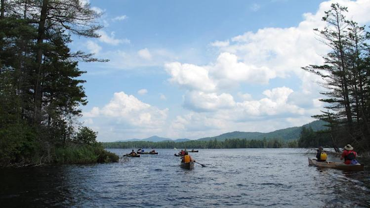 In this photo taken on Tuesday, July 8, 2014, canoeists navigate Third Lake in the Essex Chain Lakes tract near Newcomb, N.Y. The tract, which includes more than a dozen small lakes, was purchased by the state in 2012 and opened for canoe camping this summer. (AP Photo/Mary Esch)