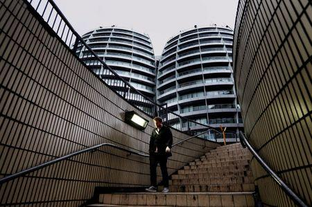 "File photo of man walking down flight of stairs near  buildings surrounding the Old Street roundabout, dubbed ""Silicon Roundabout"", in London"