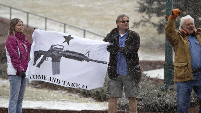 """FILE - In this March 4, 2013 file photo, opponents of proposed gun control bills being considered by the Colorado Legislature hold a sign depicting an assault rifle, displaying it to those passing in cars, in front of the State Capitol, in Denver. When a gunman opened fire inside a packed movie theater in July of 2012, killing 12, it helped revive the national debate over gun control. But, as the trial of theater shooter James Holmes is scheduled to begin Monday, April 27, 2015, Colorado's gun debate has quieted down. """"It's in a sort of gridlock,"""" said nonpartisan Denver pollster Floyd Ciruli. (AP Photo/Brennan Linsley, file)"""