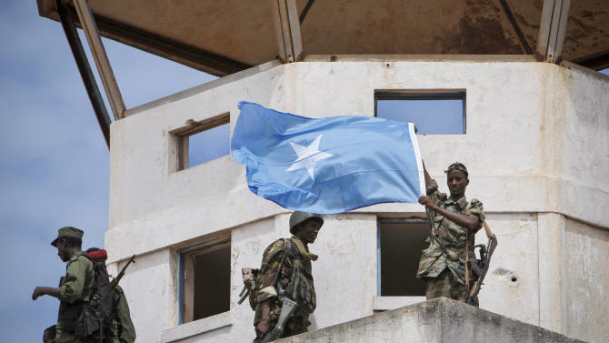 In this photo released by the African Union-United Nations Information Support Team, members of the Somali National Army and the government-allied Ras Kamboni Brigade militia display the Somali national flag from the former control tower of the airport in Kismayo, southern Somalia, Tuesday, Oct. 2, 2012. Allied African troops have taken full control of Kismayo in Somalia, the last stronghold of al-Shabab Islamist rebels who have been fighting against the country's internationally backed government, a Kenyan military official said Tuesday, and Kenya Defence Forces and the Somali National Army are now patrolling the streets. (AP Photo/AU-UN IST, Stuart Price)