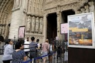 People enter in the Notre-Dame cathedral to attend a mass marking the Assumption in Paris