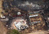 A charred vehicle sits near the remains of a home destroyed by a wildfire between Dunalley and Boomer Bay, east of the Tasmanian capital of Hobart, Australia, on Saturday, Jan. 5, 2013. Australian officials battled a series of wildfires amid scorching temperatures across the country on Saturday, with one blaze destroying dozens of homes in the island state of Tasmania. (AP Photo/Chris Kidd, Pool)