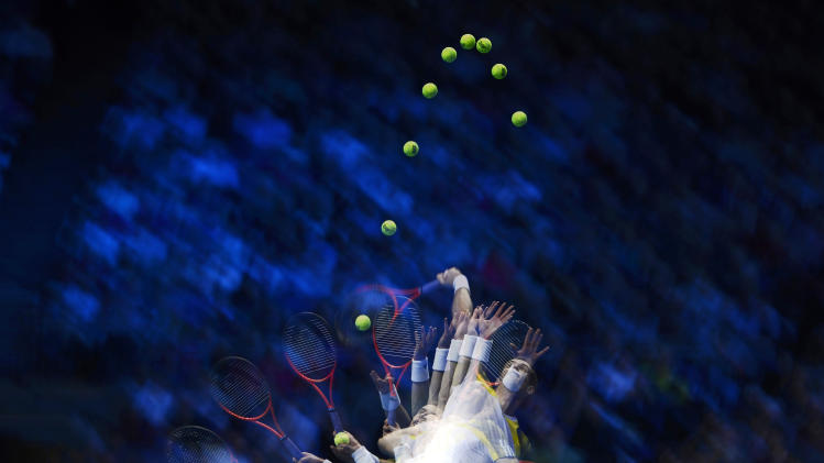 A multiple exposure photograph shows Britain's Murray as he serves to Serbia's Djokovic during their men's singles tennis match at the ATP World Tour Finals in London
