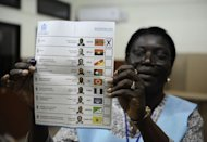An Angolan electoral agent holds up a national election ballot as she starts the counting of votes on August 31, in Viana on the outskirts of Luanda. President Jose Eduardo dos Santos was poised to extend his 33-year rule, as his party took a hefty lead in this week's vote, despite frustrations among the poor at being left out of Angola's oil boom