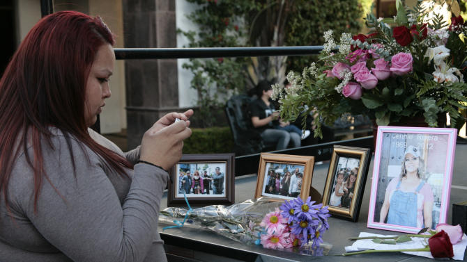 Fan Briza Jimenez takes a photo of a makeshift shrine for singer Jenni Rivera at Plaza Mexico in Lynwood, Calif. Monday, Dec. 10, 2012. U.S. authorities confirmed Monday that Jenni Rivera, a U.S.-born singer whose soulful voice and openness about her personal troubles made her a Mexican-American superstar, was killed Sunday in a plane crash in northern Mexico. (AP Photo/Jason Redmond)