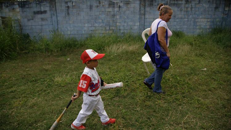In this Oct. 25, 2012 photo, Jose Andres Torres, 4, carries bats as he walks with his grandmother Dilia Barrios at a baseball school in Maracay, Venezuela. Many of the boys are inspired by the example of Detroit Tigers slugger Miguel Cabrera, who learned the game on the very field. Their baseball school in the poor neighborhood where Cabrera grew up is one of many across Venezuela, a web for training young ballplayers that has made the country a powerhouse in the U.S. major leagues. (AP Photo/Ariana Cubillos)