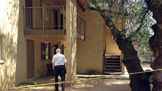A police volunteer stands outside an apartment in Payson, Ariz., Tuesday, May 27, 2014, after a 3-year-old boy shot and killed his 1½ -year-old brother, according to Police Chief Don Engler. According to authorities, the boys found a handgun in a neighbor's apartment and took it to another room where the shooting occurred. (AP Photo/Payson Roundup, Alexis Bechman)