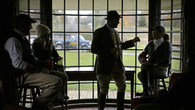 In this Nov. 8, 2014 photo, Elkridge-Harford Hunt Club president Jay Young, second from right, talks with members at a tea party in the clubhouse following a hunt in Monkton, Md. (AP Photo/Patrick Semansky)