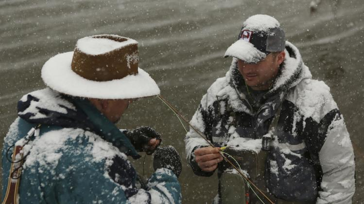 Fly fishermen retie their lures during a winter blizzard in Hopeville Canyon, West Virginia
