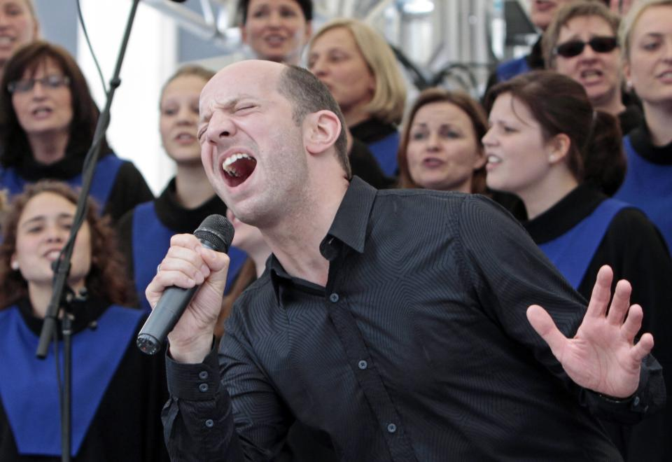 In this Thursday, July 12, 2012 photo, Roland Orthaus, director of Gospelchoir Rejoice, from Langenberg, Germany, performs, on Fountain Square in Cincinnati. Hundreds of choirs from around the world are competing in 23 categories in the event that ends Saturday. (AP Photo/Al Behrman)