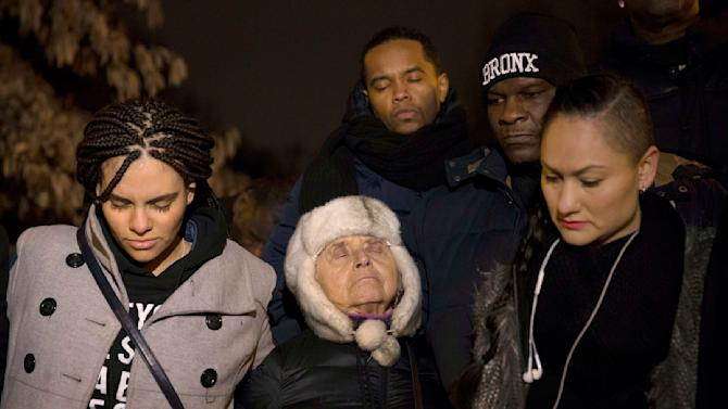People pause in silence as they gather near Central Park in Harlem