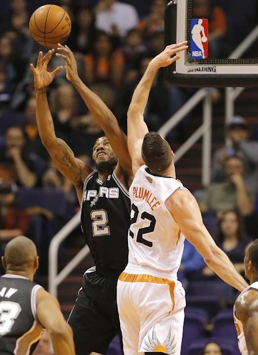 San Antonio Spurs' Kawhi Leonard (2) pulls down a rebound next to Phoenix Suns' Miles Plumlee (22) during the first half of an NBA basketball game, Wednesday, Dec. 18, 2013, in Phoenix