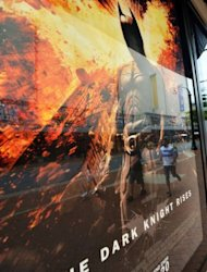 "People walk past a poster of the new Batman movie ""The Dark Knight Rises"" outside a theater in Silver Spring, Maryland. With a fixation on random violence, Gotham City dysfunction and the death of a star, the ""Batman"" movies have long been consumed with tragedy and terror. Now an unfathomable horror is forever linked to the series"
