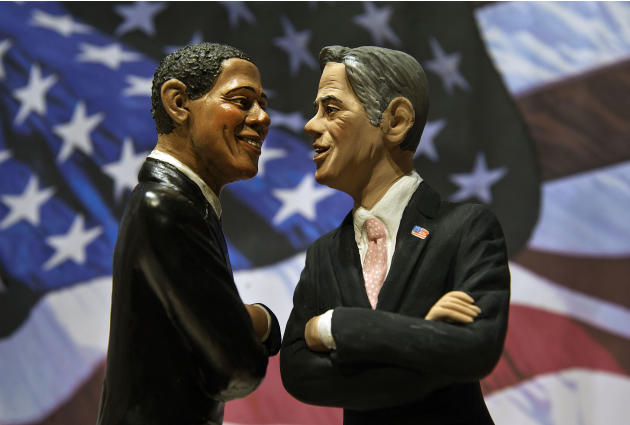 Two statuettes depicting President Barack Obama, left, and Republican rival Mitt Romney are backdropped by the Stars and Stripes in a shop which sells Christmas nativity figures in Naples, Italy, Mond