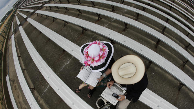Steve and Florence Wright, from Phoenix, study their racing program before the running of the 139th Kentucky Oaks at Churchill Downs Friday, May 3, 2013, in Louisville, Ky. Saturday will be the 139th running of the Kentucky Derby. (AP Photo/Charlie Riedel)