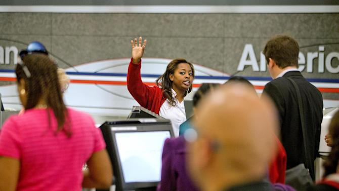 FILE - In this Tuesday, April 16, 2013, file photo, an American Airlines ticket agent talks assists passengers checking in at Hartsfield-Jackson airport, in Atlanta. AMR Corp. reports quarterly financial results before the market opens on Wednesday, April 17, 2013. (AP Photo/David Goldman)