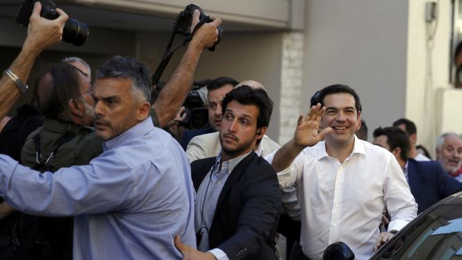 Greek Prime Minister Alexis Tsipras waves outside a polling station where he voted in national referendum in Athens