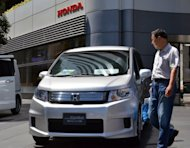 A customer looks a Honda Motor vehicle at the company&#39;s showroom in Tokyo. Honda said Tuesday its net profit surged more than fourfold to $1.7 billion for the three months to June, underscoring a recovery from the impact of last year&#39;s quake-tsunami disasters