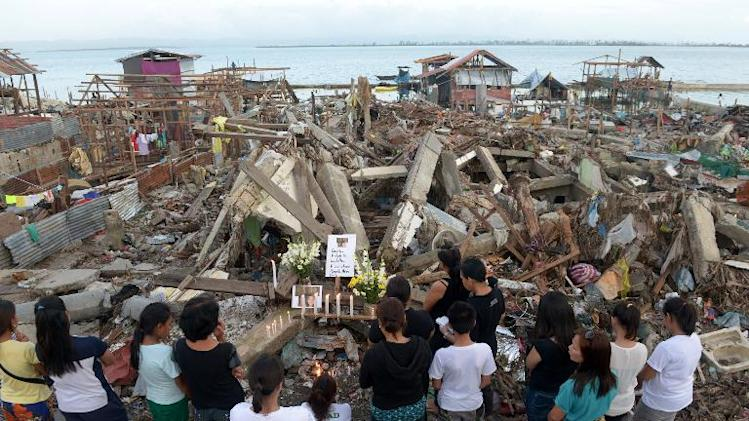 Relatives offer flowers and light candles in Tacloban on December 17, 2013 at the ruins of a house once lived in by family members