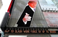An image of Donald Trump is seen above a message board announcing job cuts at Hewlett-Packard in New York&#39;s Times Square on May 17. The move came as the California-based firm reported a 31% drop in profits in its second fiscal quarter to $1.6 bn