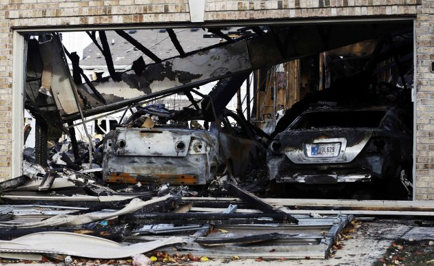 Two cars sit in a home that was heavily damaged by a explosion, Sunday, Nov. 11, 2012, in Indianapolis. Nearly three dozen homes were damaged or destroyed, and seven people were taken to a hospital wi