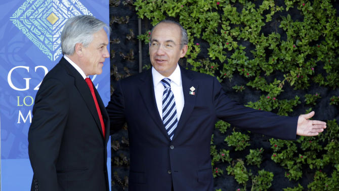 Chile's President Sebastian Pinera, left, is welcomed by Mexico's President Felipe Calderon during the opening session of the G20 Summit in Los Cabos, Mexico, Monday, June 18, 2012. (AP Photo/Eduardo Verdugo)